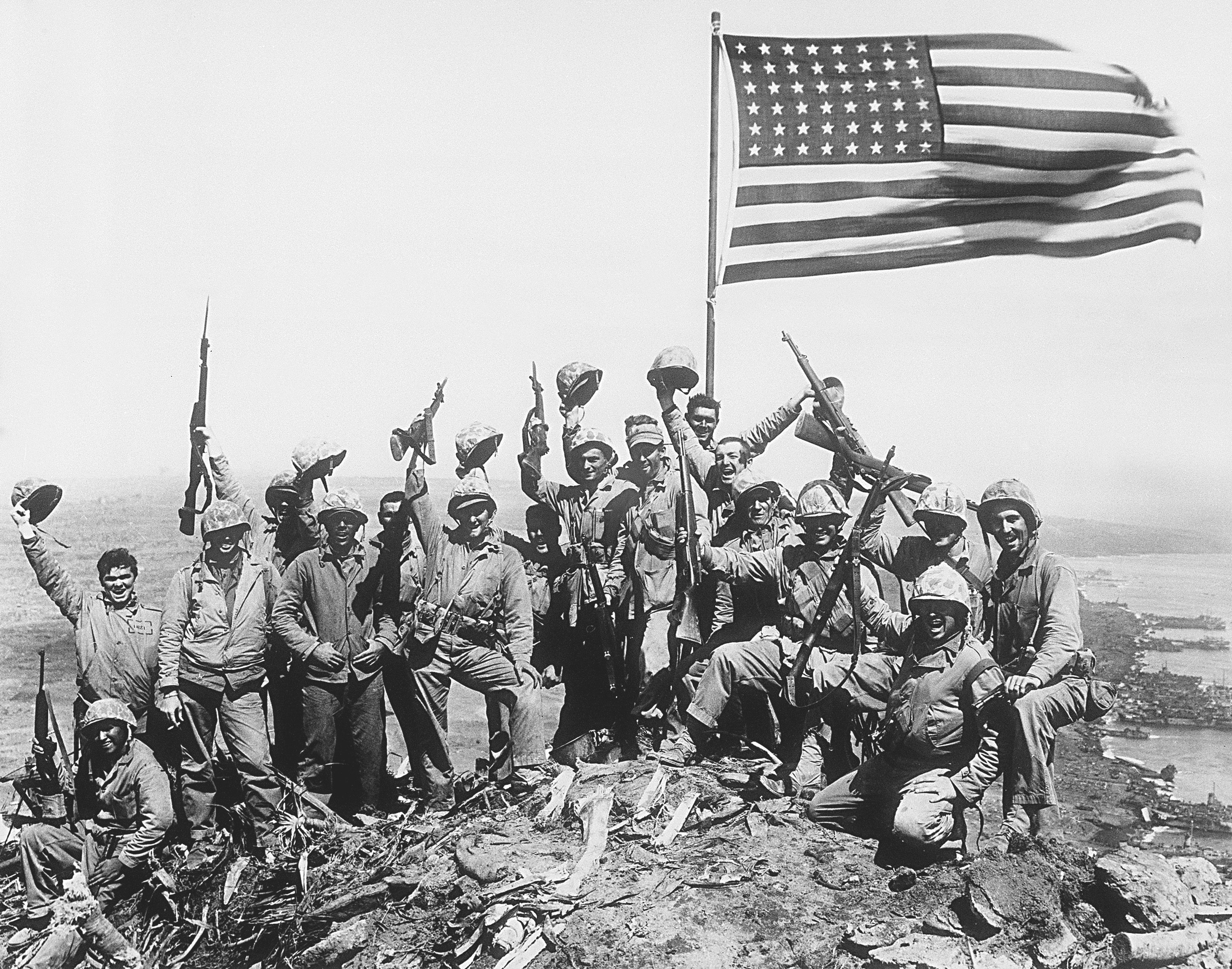 U.S. Marines of the 28th Regiment, fifth division, cheer and hold up their rifles after raising the American flag atop Mount Suribachi on Iwo Jima, a volcanic Japanese island, on Feb. 23, 1945 during World War II.  (AP Photo/Joe Rosenthal)
