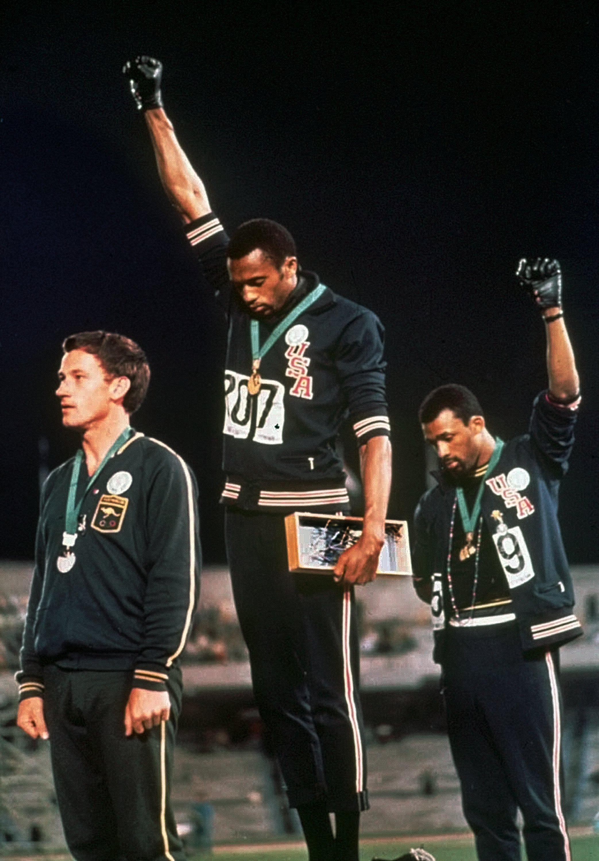 Extending gloved hands skyward in racial protest, U.S. athletes Tommie Smith, center, and John Carlos stare downward during the playing of the Star Spangled Banner after Smith received the gold and Carlos the bronze for the 200 meter run at the Summer Olympic Games in Mexico City on Oct. 16, 1968. AP Photo/FILE.
